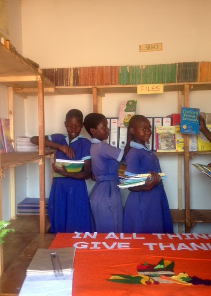 Children of Masuwe School putting their books in the newly built book shelves Victoria Falls, Zimbabwe
